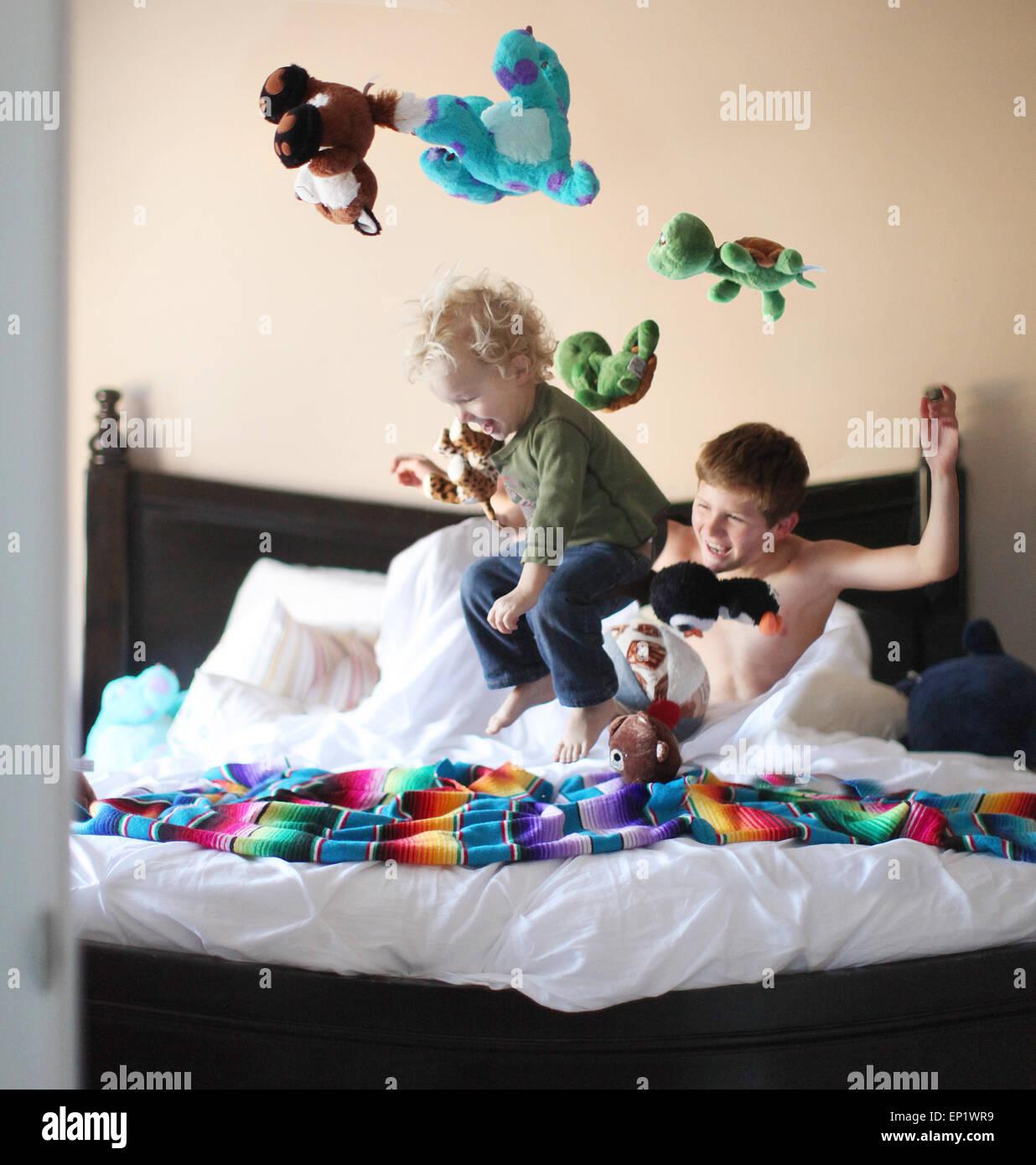 Ragazzo di saltare sul letto di fratelli e gettando i peluche in aria Immagini Stock