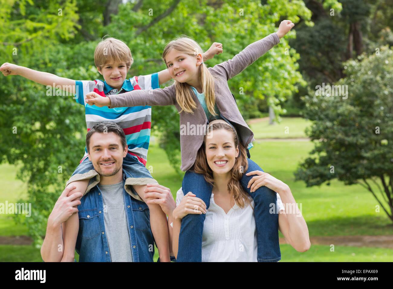 Genitori felici che trasportano i bambini sulle spalle in posizione di parcheggio Immagini Stock