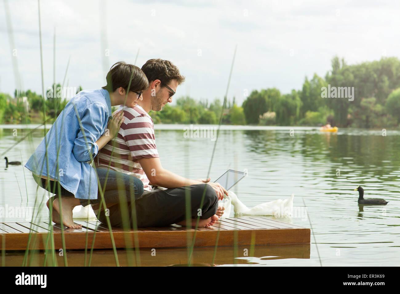 Giovane utilizzando il computer portatile sul dock Immagini Stock