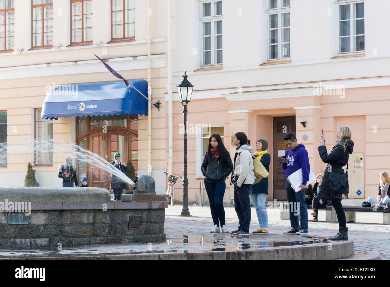Un gruppo di turisti prestando attenzione ad una fontana a Tartu in Estonia Immagini Stock