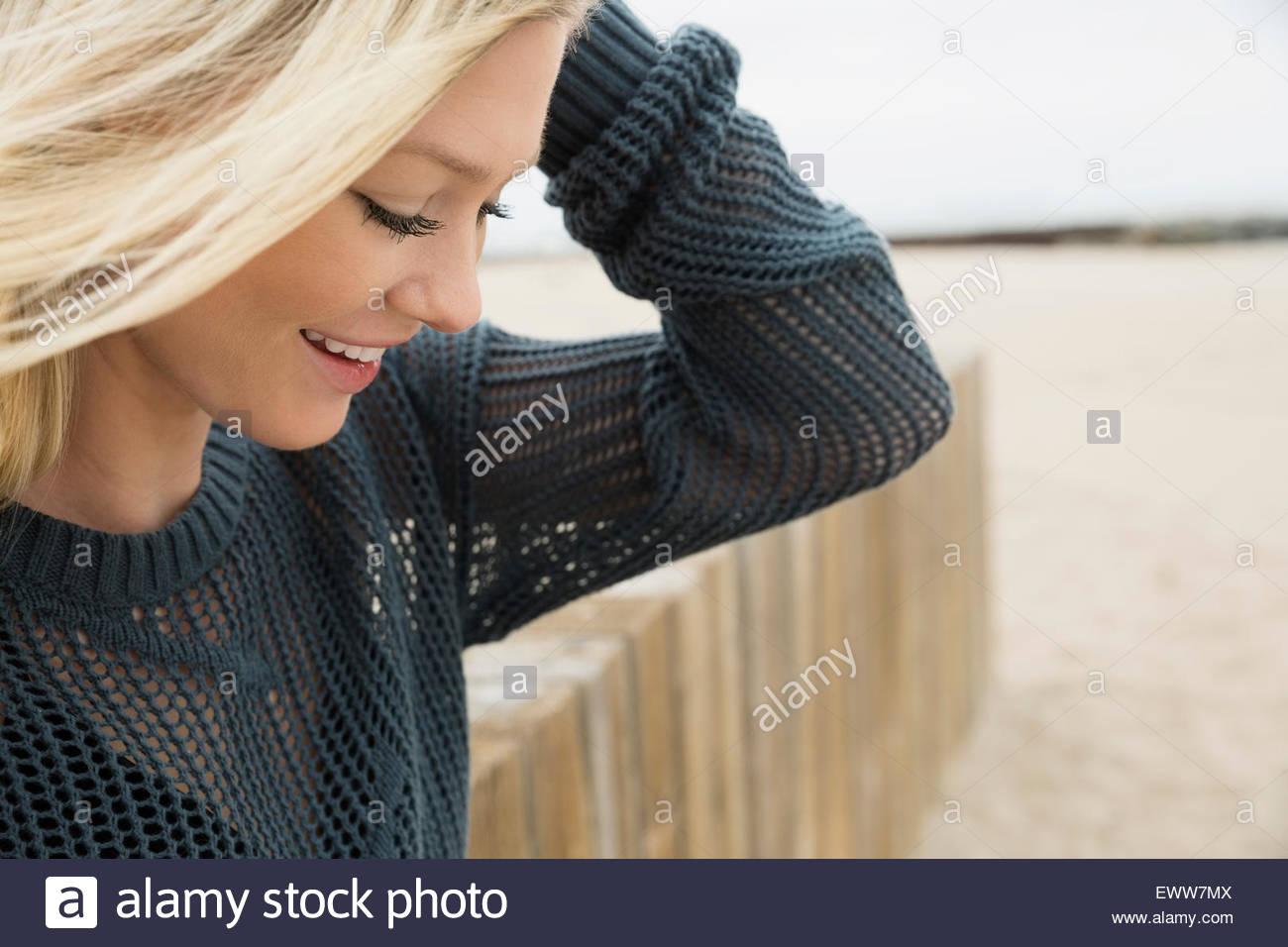 Donna bionda guardando giù in spiaggia Immagini Stock