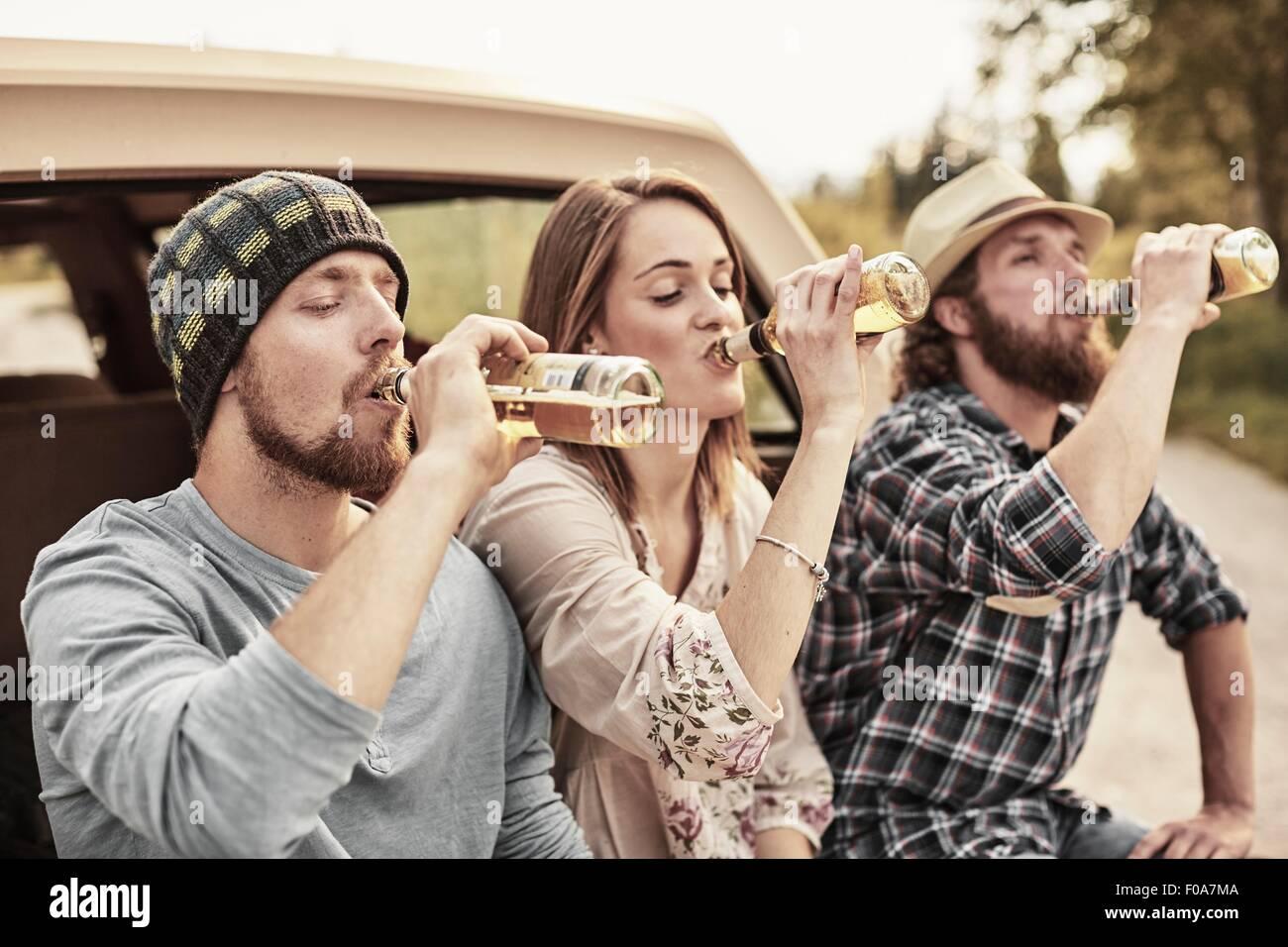 Tre persone a bere birra in bottiglia unisono Immagini Stock