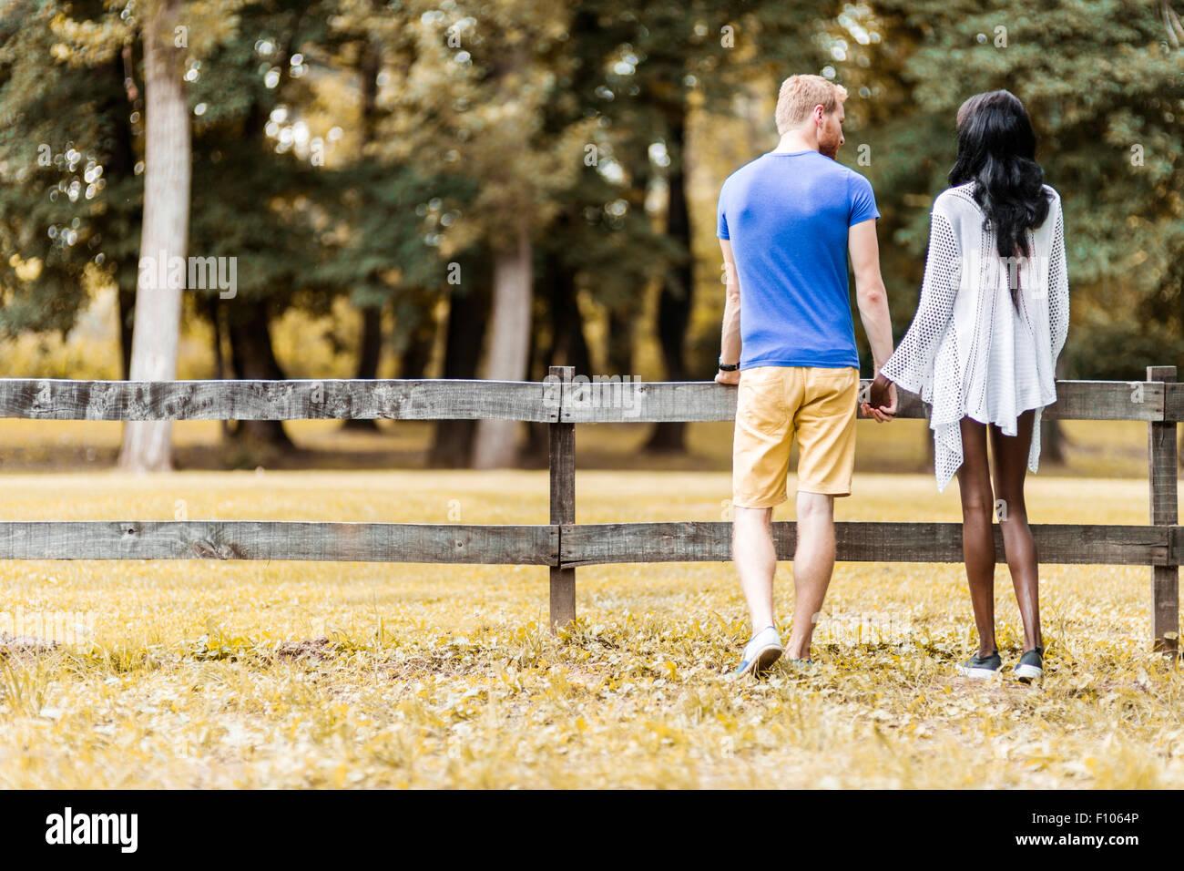 Coppia felice in amore tenendo le mani in un parco in autunno Immagini Stock