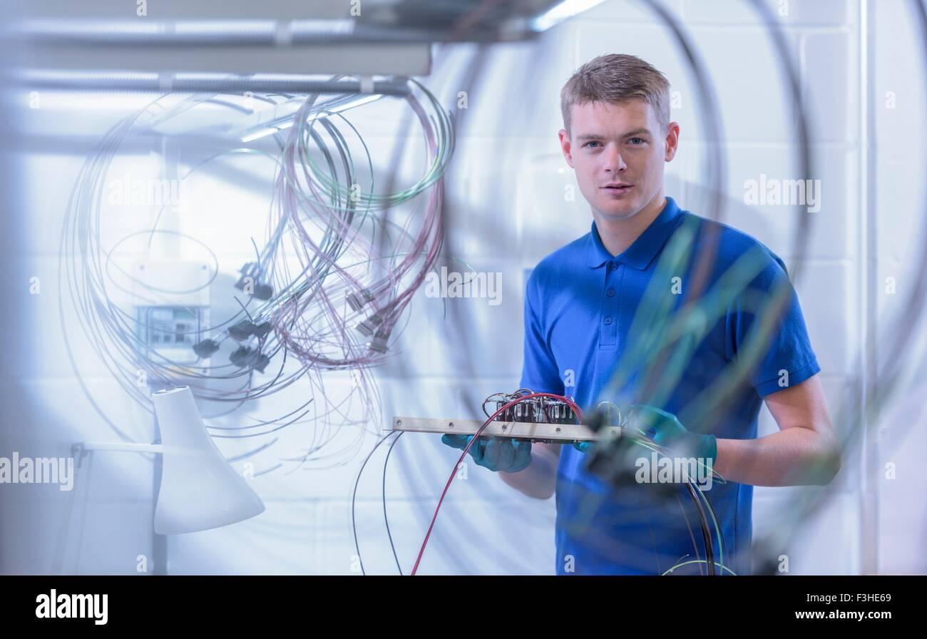 Ritratto di apprendista electronics lavoratore in fabbrica di componenti elettronici, Immagini Stock