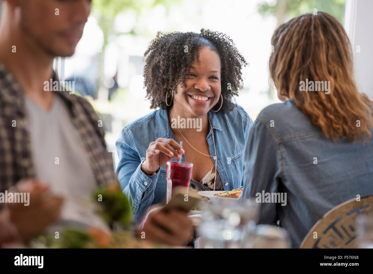 Tre persone seduti ai tavoli in una caffetteria. Due donne ridere. Immagini Stock