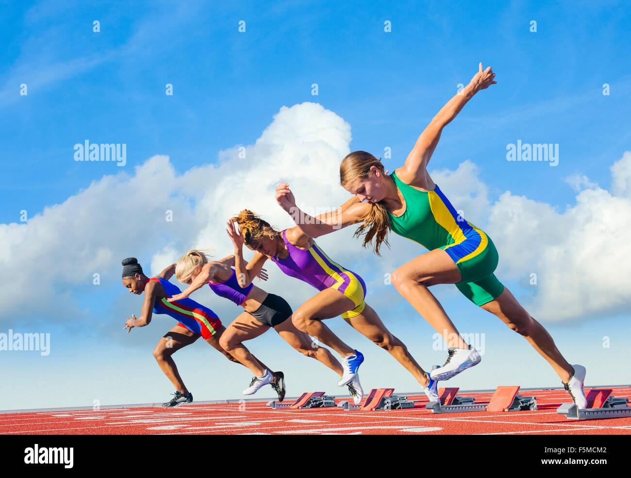 Quattro atlete sulla pista di atletica, gara di partenza Immagini Stock