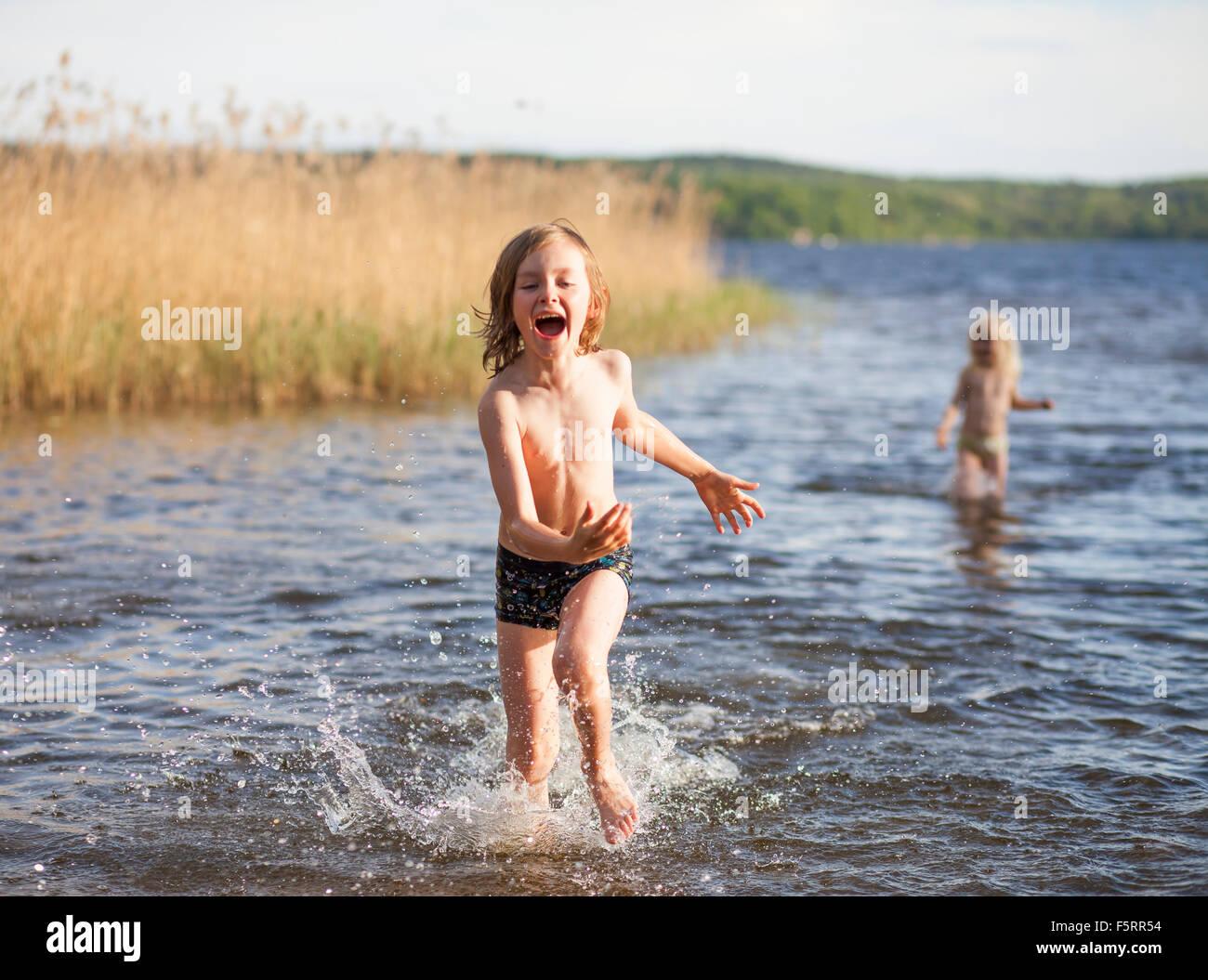 La Svezia, Vastergotland, Lerum, lago Aspen, ragazzo (8-9) e la ragazza (6-7) giocando a lago Immagini Stock
