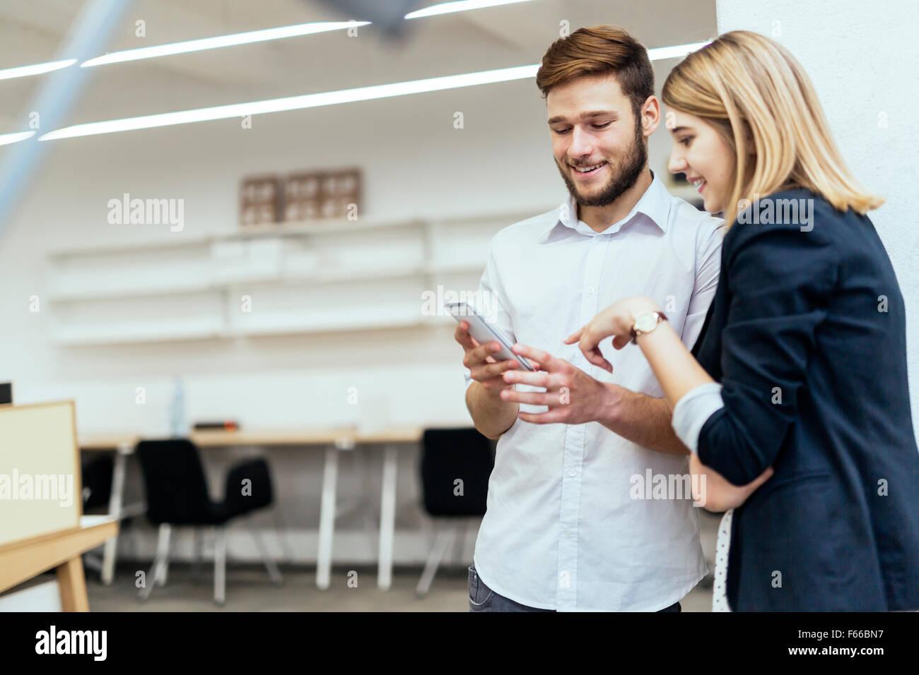 I colleghi ridere insieme in ufficio durante il lavoro Immagini Stock