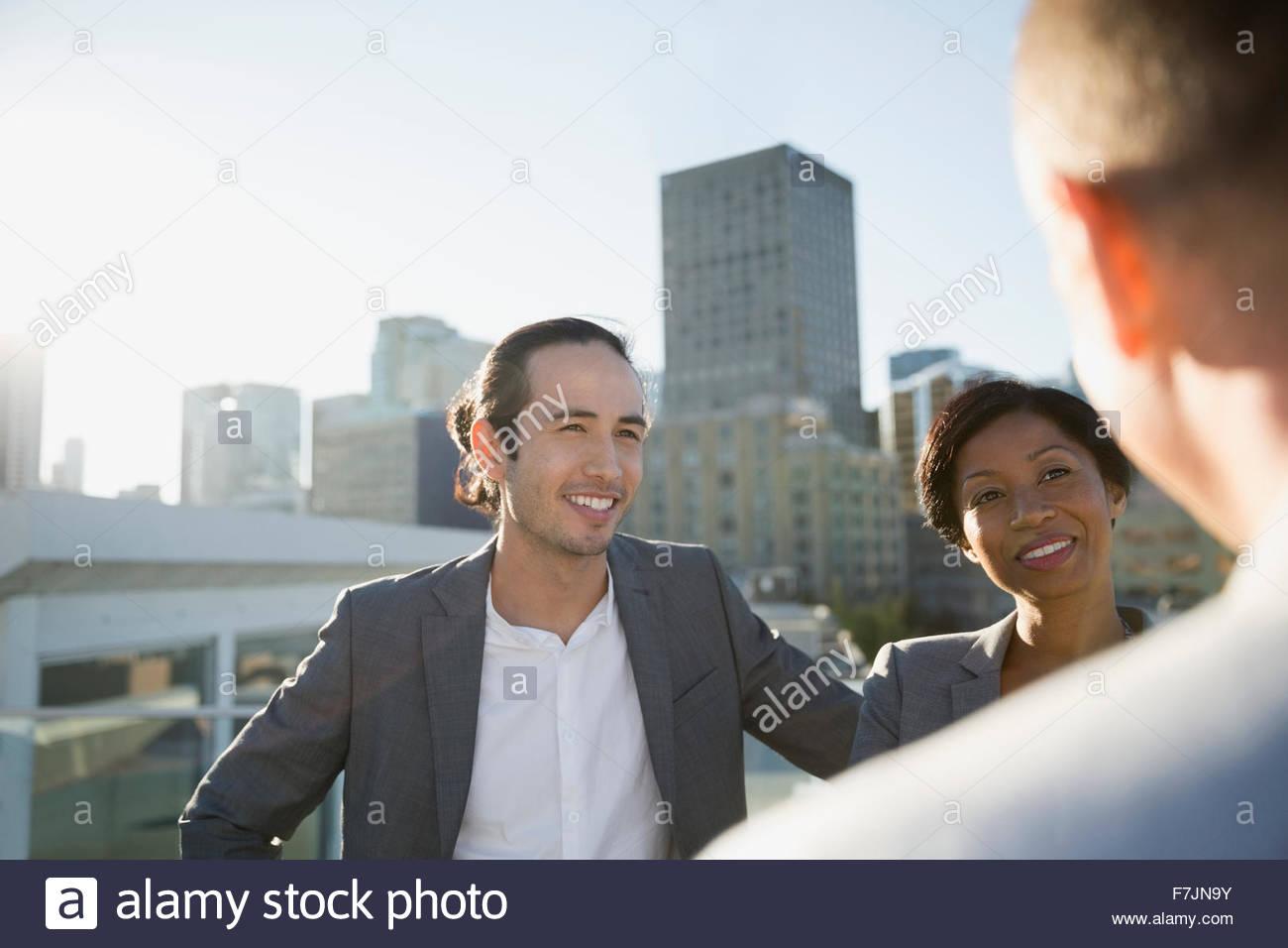 La gente di affari di parlare sul soleggiato sul tetto urbano Immagini Stock
