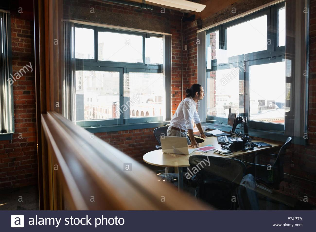Imprenditore pensieroso a guardare fuori dalla finestra di ufficio Immagini Stock