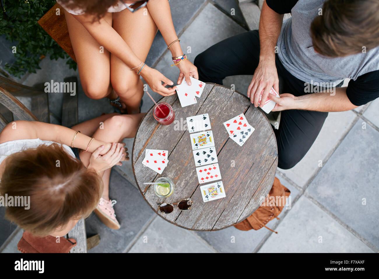 Vista superiore di tre giovani giocando a carte cafè sul marciapiede. I giovani seduti attorno a un tavolo Immagini Stock