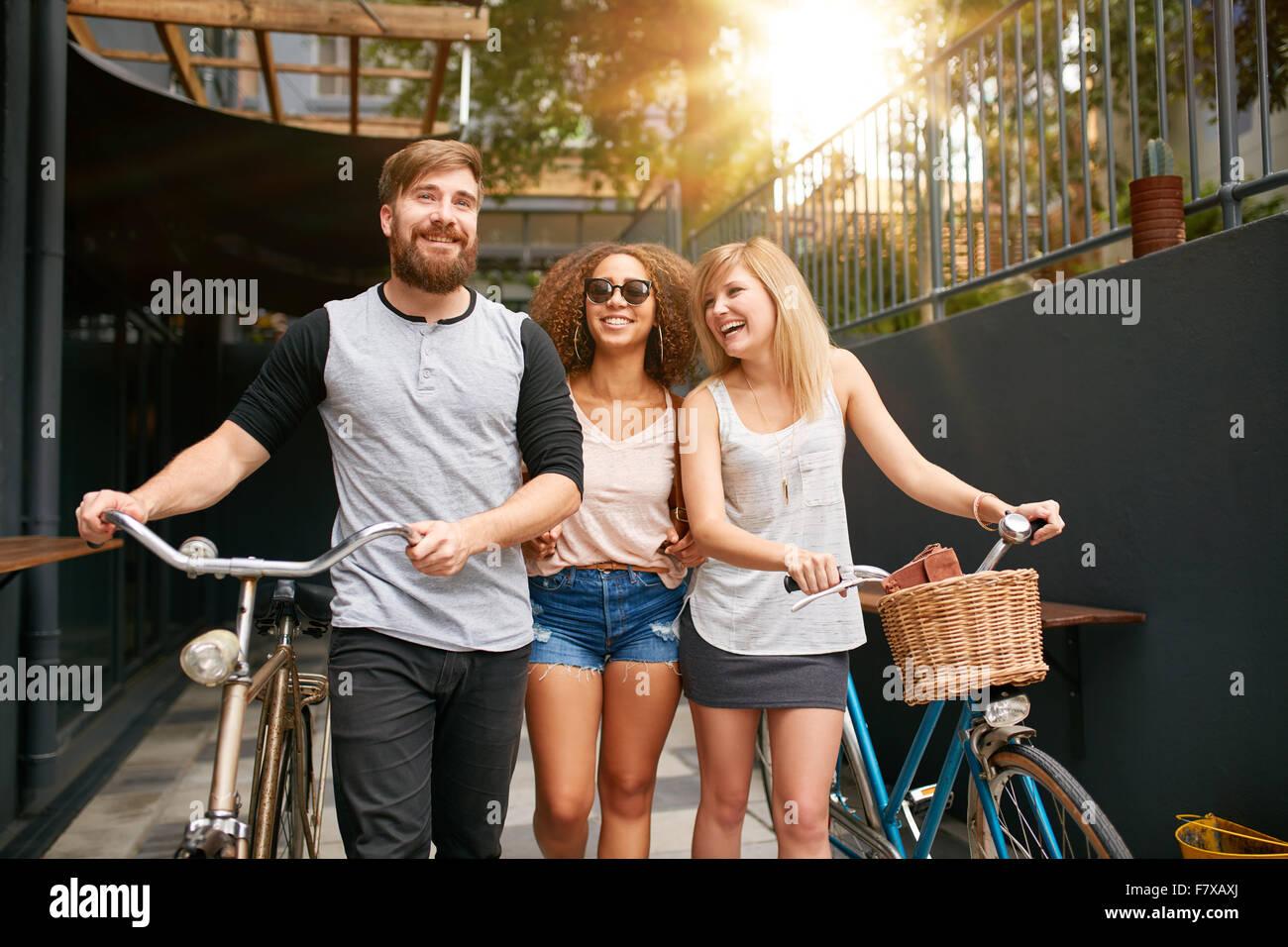 Tre giovani camminando per la strada con le loro biciclette e divertirsi. Maschio e femmina di amici con le loro Immagini Stock