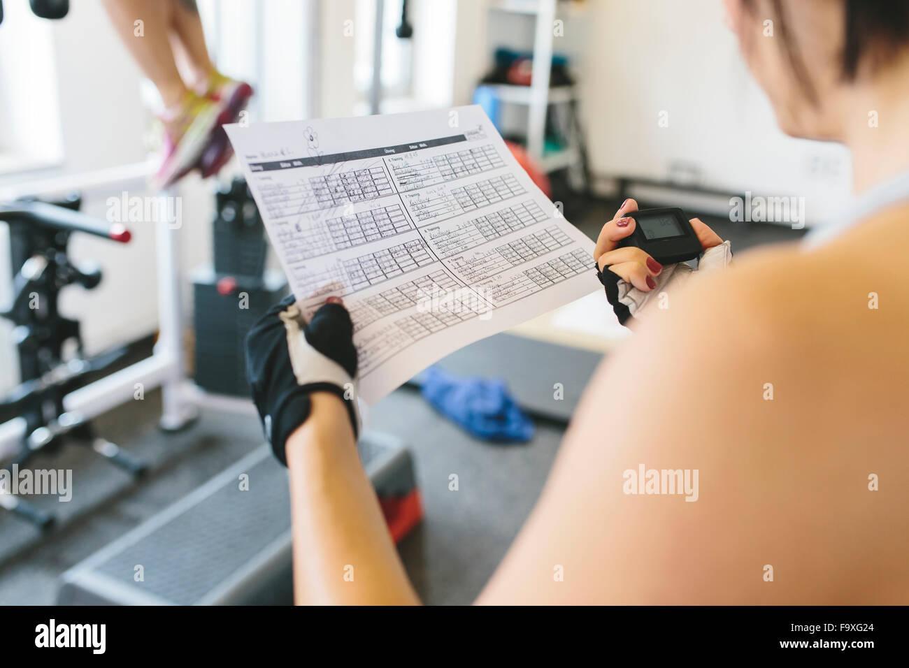Donna prendendo il tempo mentre atleta facendo pull-up in palestra Immagini Stock