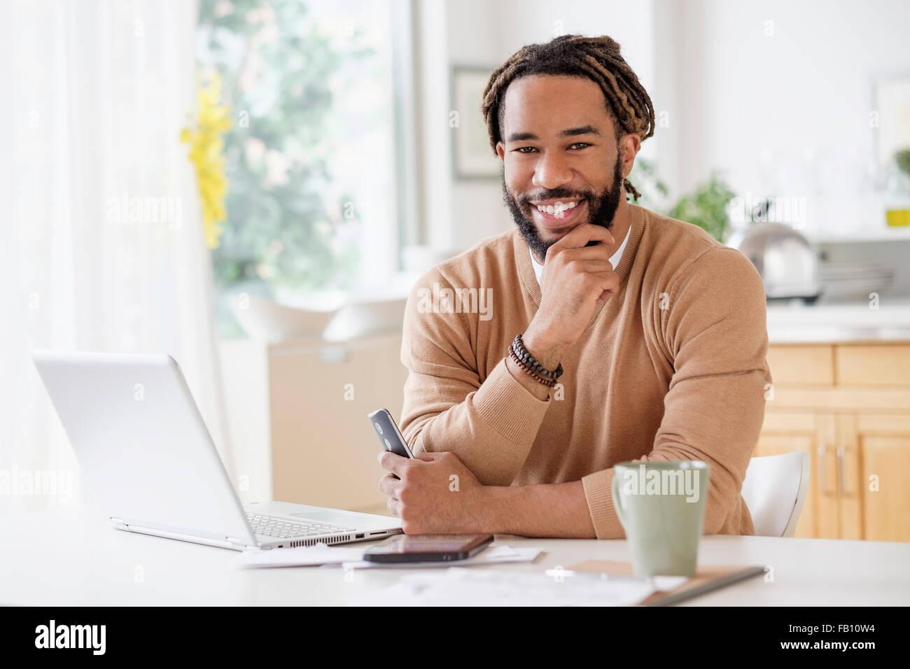 Ritratto di giovane smiley Uomo con notebook a tavola Immagini Stock