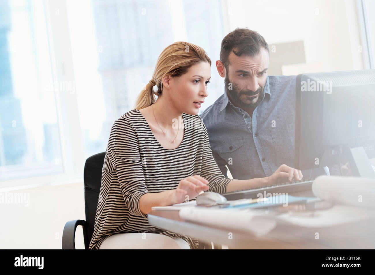 Uomo e donna che guarda al computer in ufficio Immagini Stock