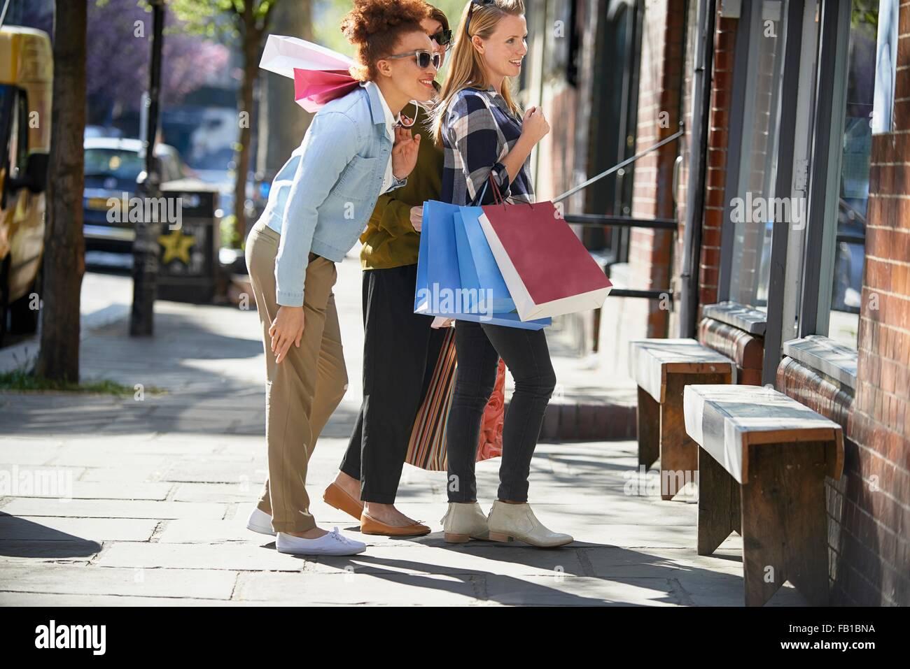 Vista laterale di donne tenendo le borse della spesa in piedi in strada guardando in vetrina Immagini Stock