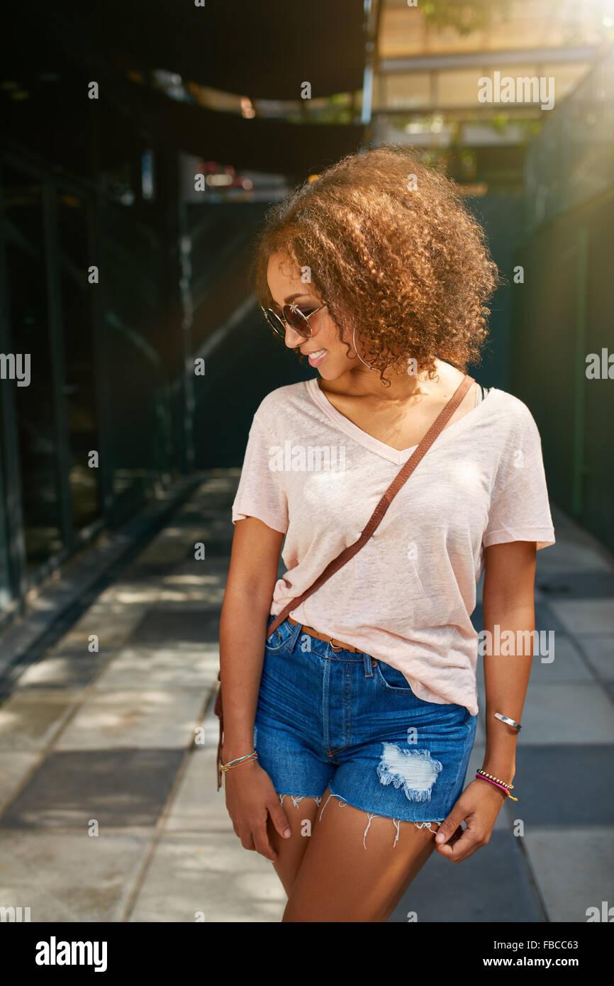 Giovane americano africano ragazza di città. Indossa abbigliamento casual, occhiali da sole e guardare verso Immagini Stock