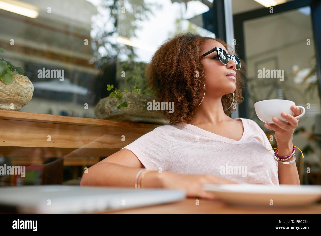 Ritratto di giovane attraente ragazza africana avente una tazza di caffè presso il cafe. Elegante ragazza di Immagini Stock