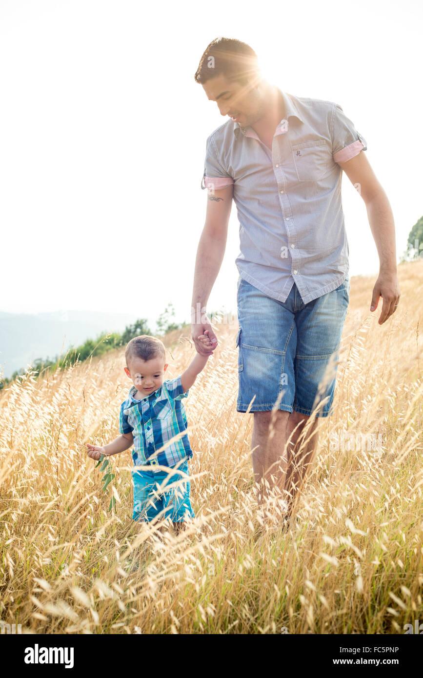 Uomo e ragazzo camminare attraverso il campo Immagini Stock