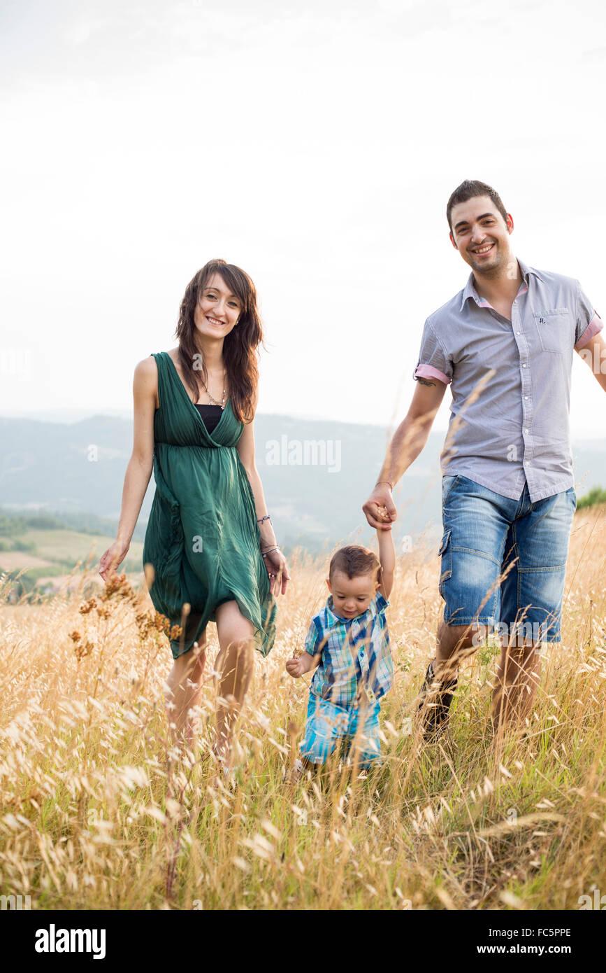 Sorridendo i genitori a piedi con giovane figlio nel campo Immagini Stock