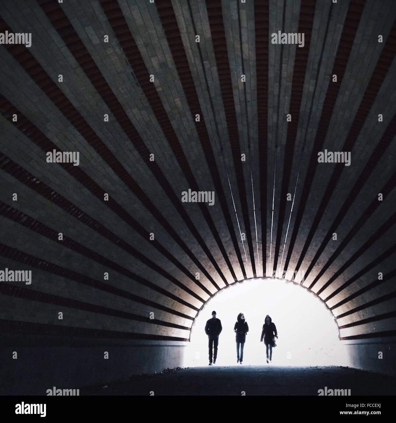 A lunghezza piena di gente camminare nel tunnel Immagini Stock