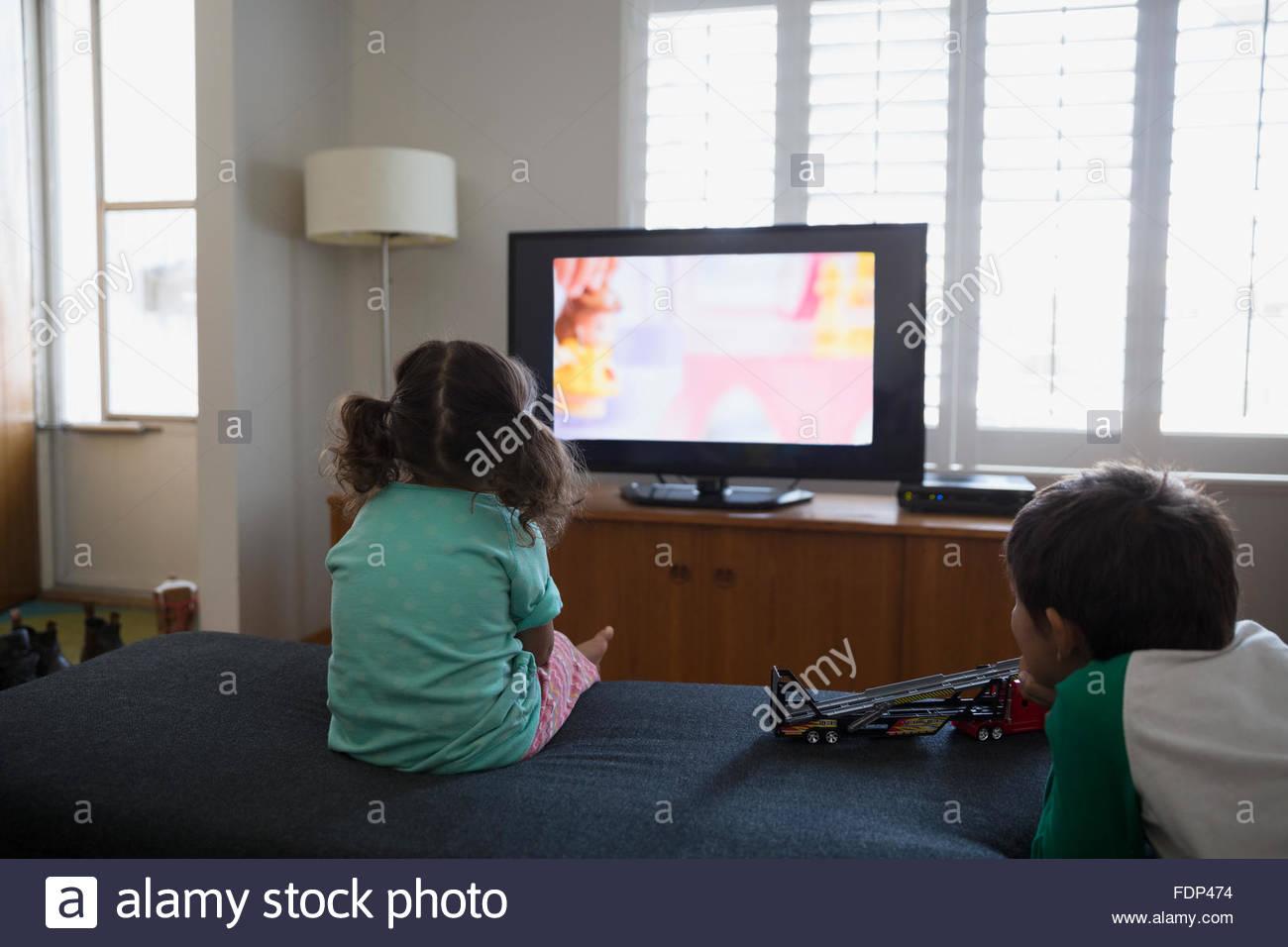 Fratello e Sorella guardando cartoni animati in salotto Immagini Stock