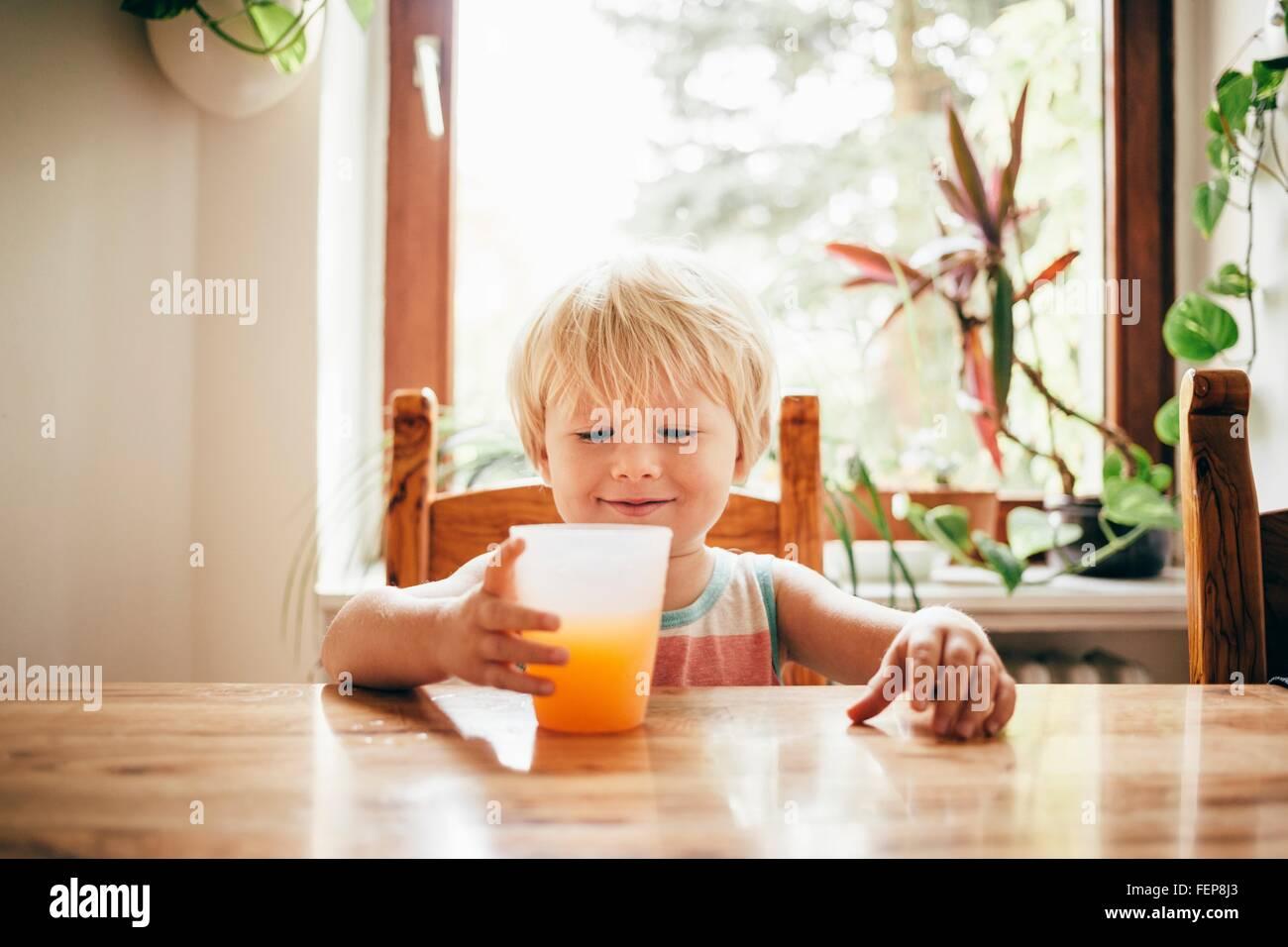 Ragazzo seduto a tavola con bicchiere di succo di arancia guardando giù sorridente Immagini Stock