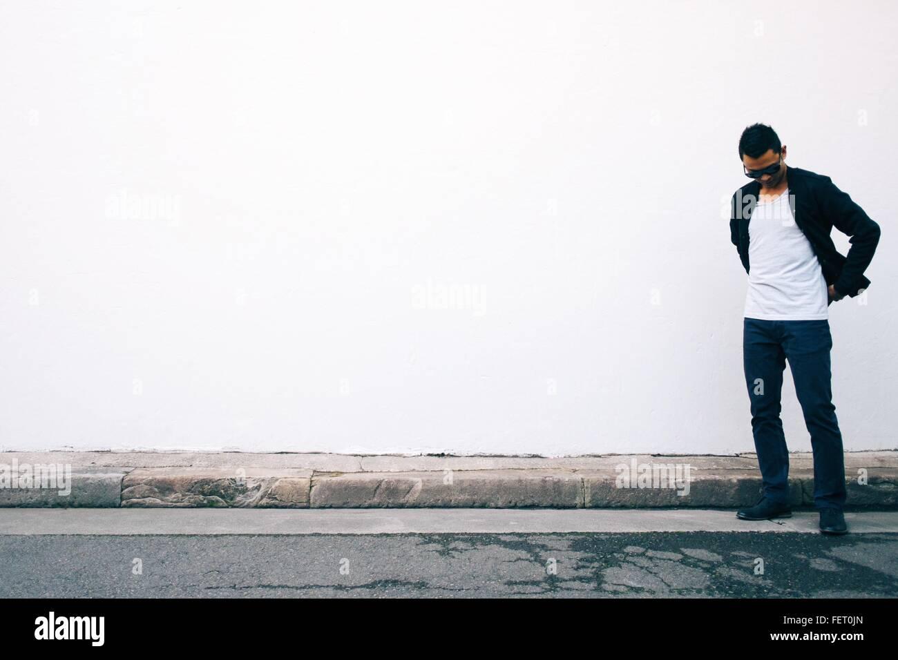Giovane uomo guardando giù in piedi contro il muro bianco Immagini Stock
