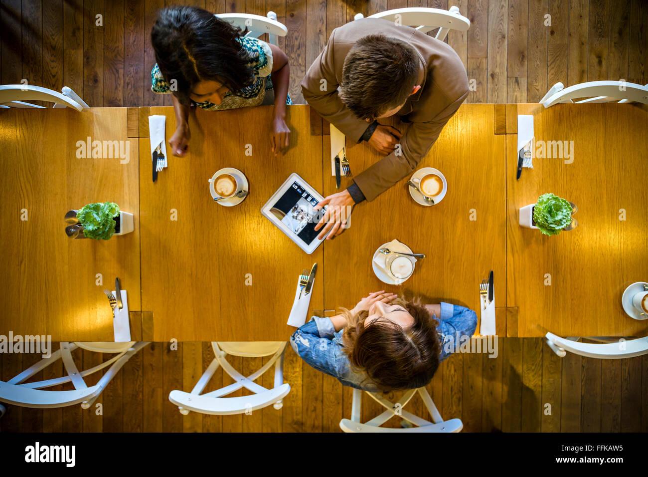 Amici utilizzando la tavoletta digitale nel ristorante Immagini Stock