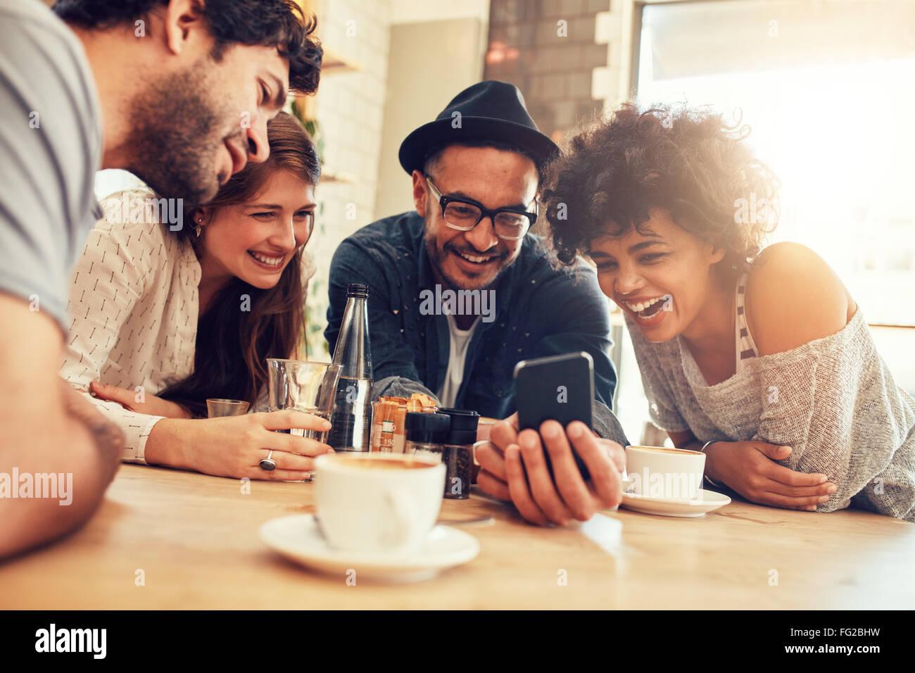 Ritratto di Allegro giovani amici guardando smart phone mentre è seduto al cafe'. Razza mista persone sedute Immagini Stock