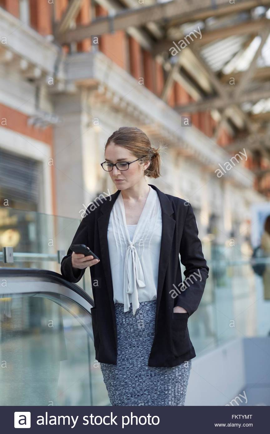 Imprenditrice su escalator guardando giù smartphone Immagini Stock
