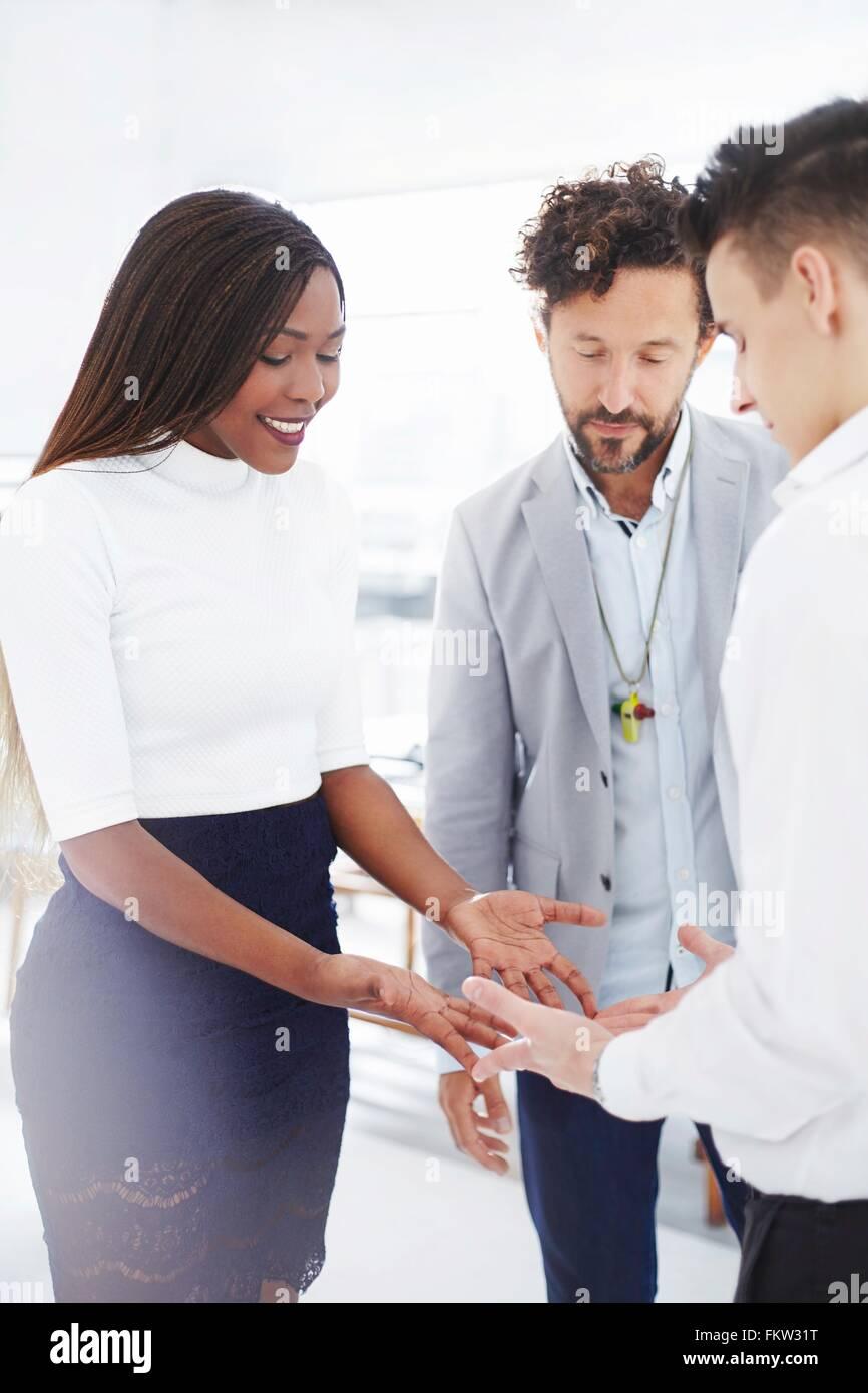 I colleghi di team building task faccia a faccia tenendo le mani guardando giù sorridente Immagini Stock