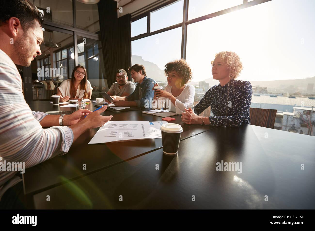 Ritratto del team Creative seduti attorno a un tavolo per discutere di nuovi piani di progetto. Razza mista persone Immagini Stock