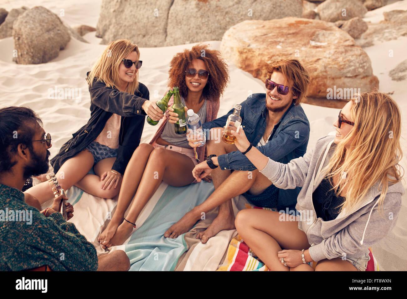 Un gruppo di giovani birre di tostatura mentre è seduto sulla spiaggia. Razza mista amici celebrando con bevande Immagini Stock
