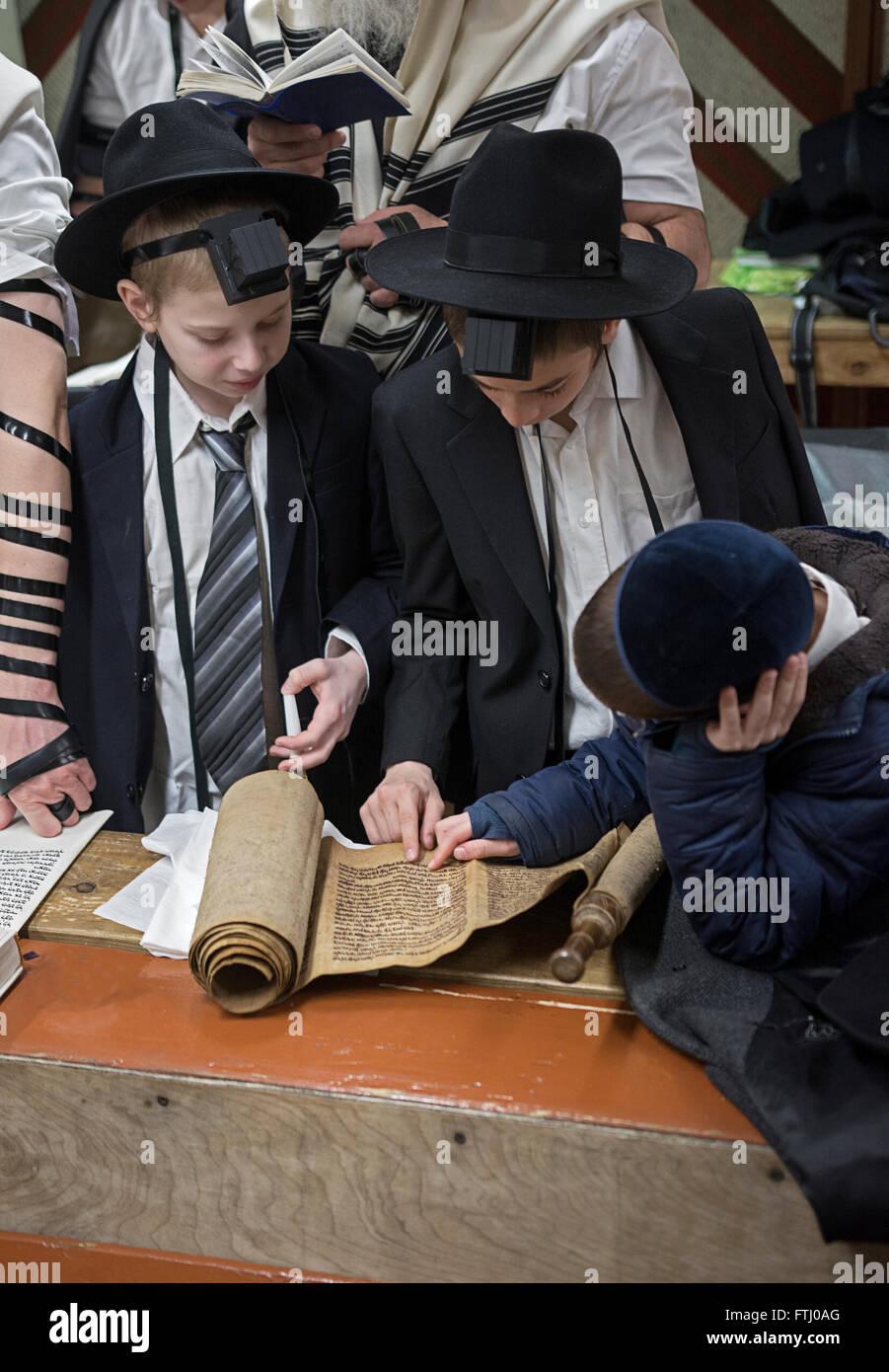 Religiosa ebraica degli adolescenti di ascoltare la lettura della Megillah sulla festa di Purim in una sinagoga Immagini Stock
