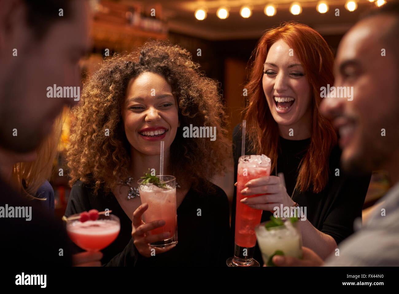 Gruppo di amici riuniti per un drink serale nel Cocktail Bar Immagini Stock
