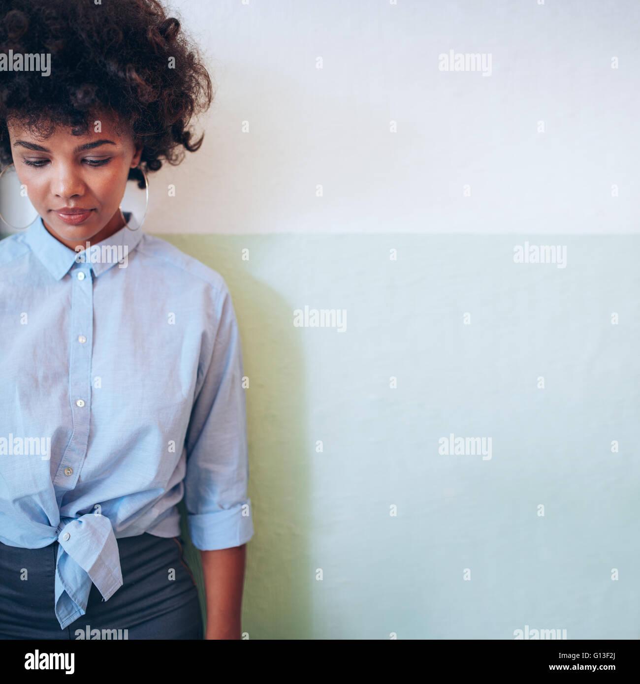 Immagine ritagliata della giovane e bella donna africana in piedi contro un muro e guardando verso il basso. Gara Immagini Stock