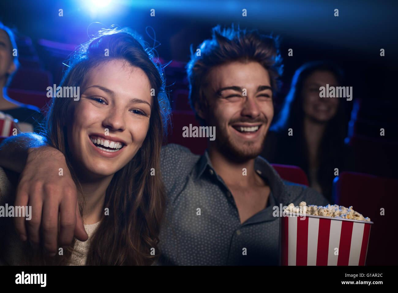 Felice coppia giovane nel cinema a guardare un film e sorridente, di intrattenimento e di stare insieme concetto Immagini Stock