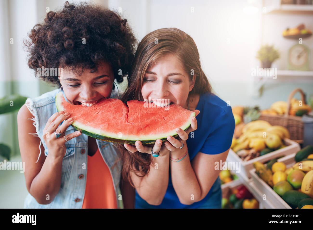 Due giovani donna mangiare anguria e divertirsi. Razza mista amiche insieme a mangiare una fetta di anguria. Immagini Stock