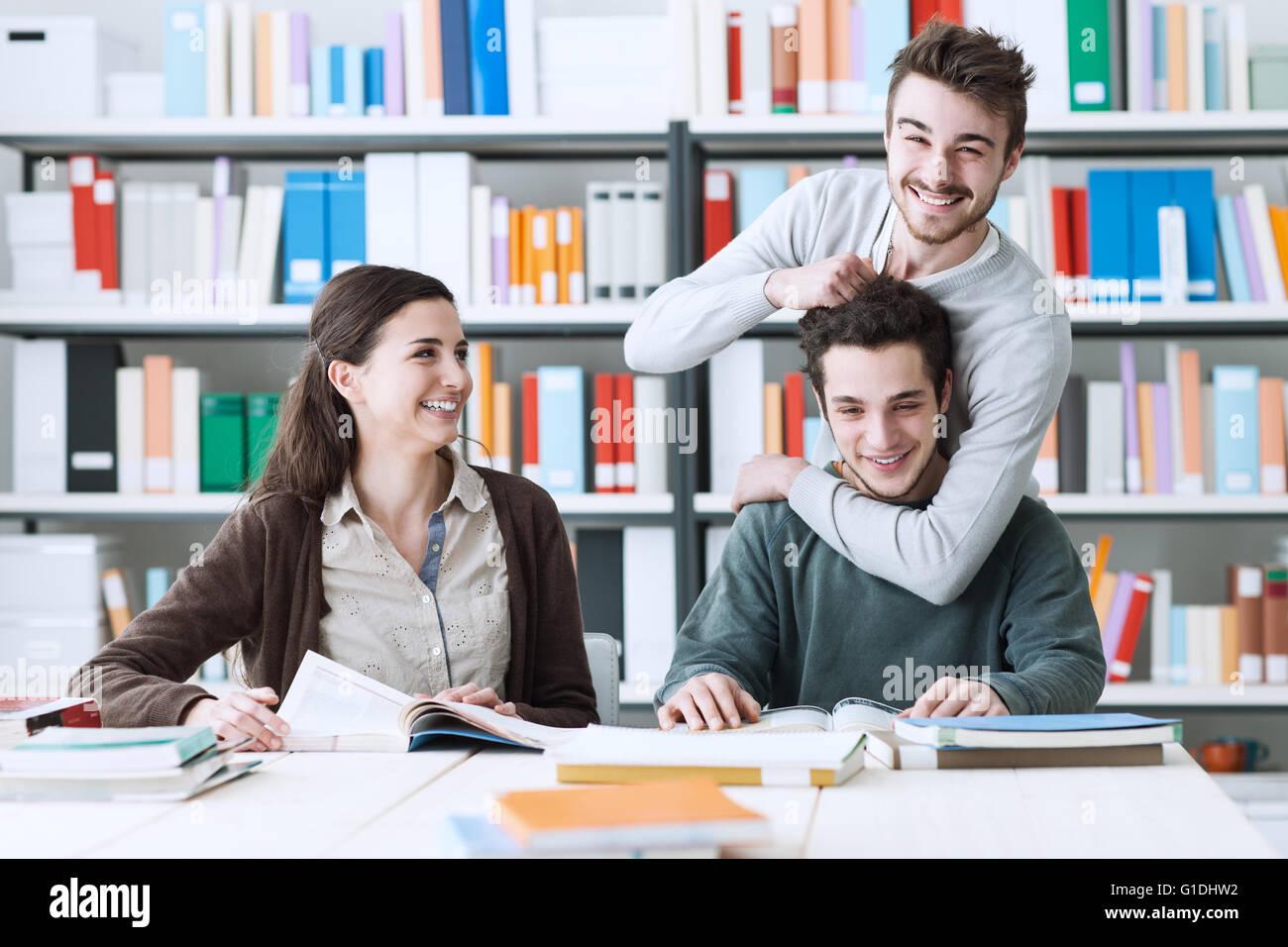 Giocoso schoolmates studiando insieme alla biblioteca, di stare insieme e di concetto di amicizia Immagini Stock