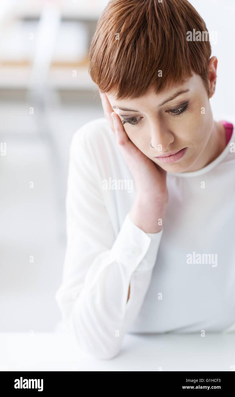 Triste premuto giovane donna seduta alla scrivania e guardando verso il basso, lei è appoggiata sulla sua mano, Immagini Stock