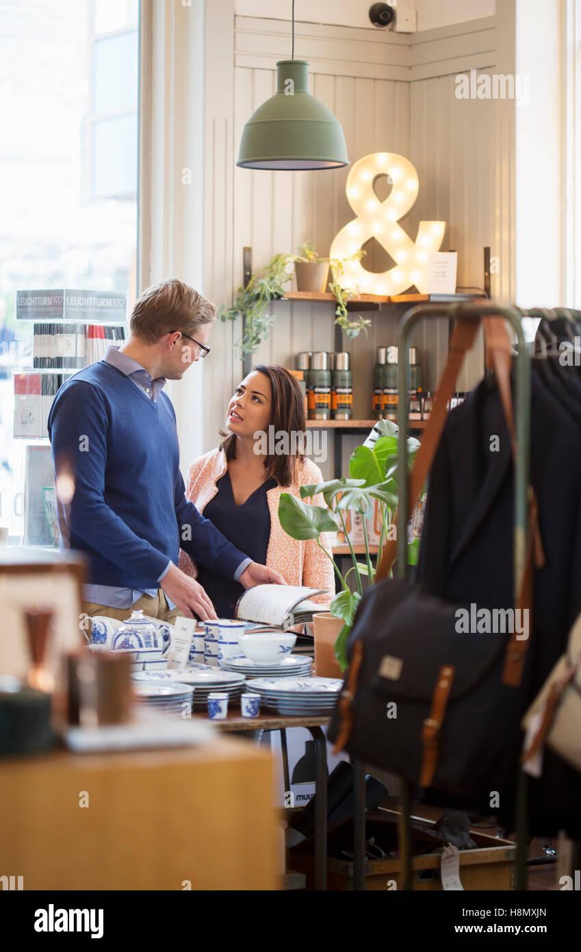 Coppia giovane parlando in negozio Immagini Stock