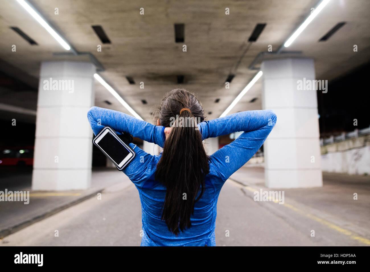 Giovani runner sotto il ponte di sera, in appoggio Immagini Stock