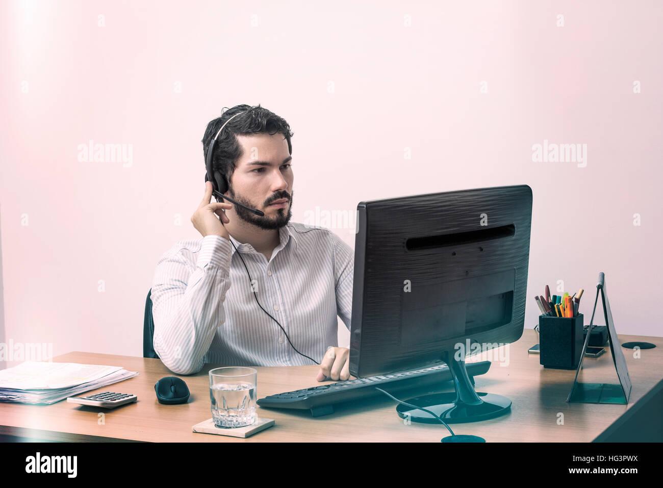 Giovane uomo durante la chiamata telefonica guardando il monitor e prestando attenzione. Immagini Stock