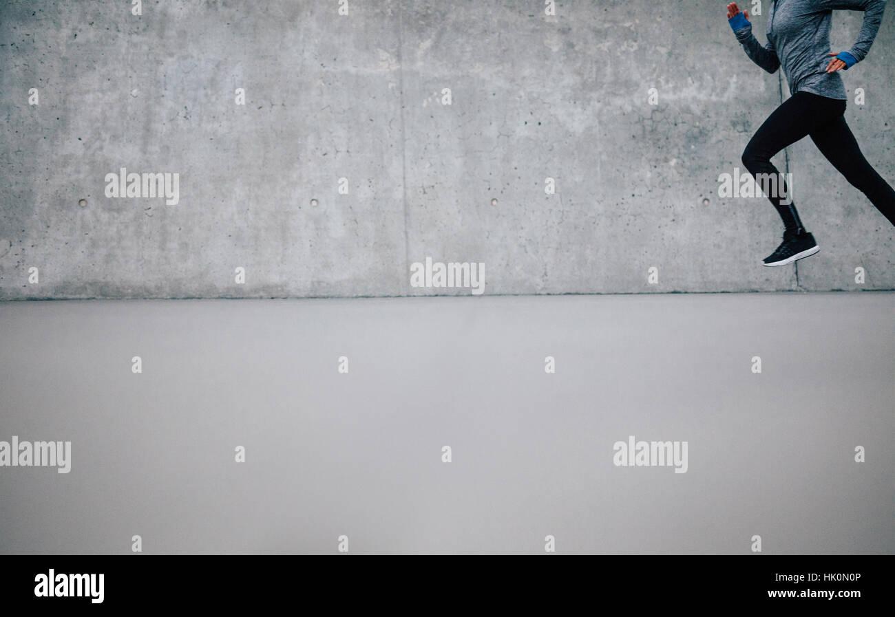 Runner atleta che corre su sfondo grigio. Donna Fitness jogging con un sacco di spazio copia. Immagini Stock