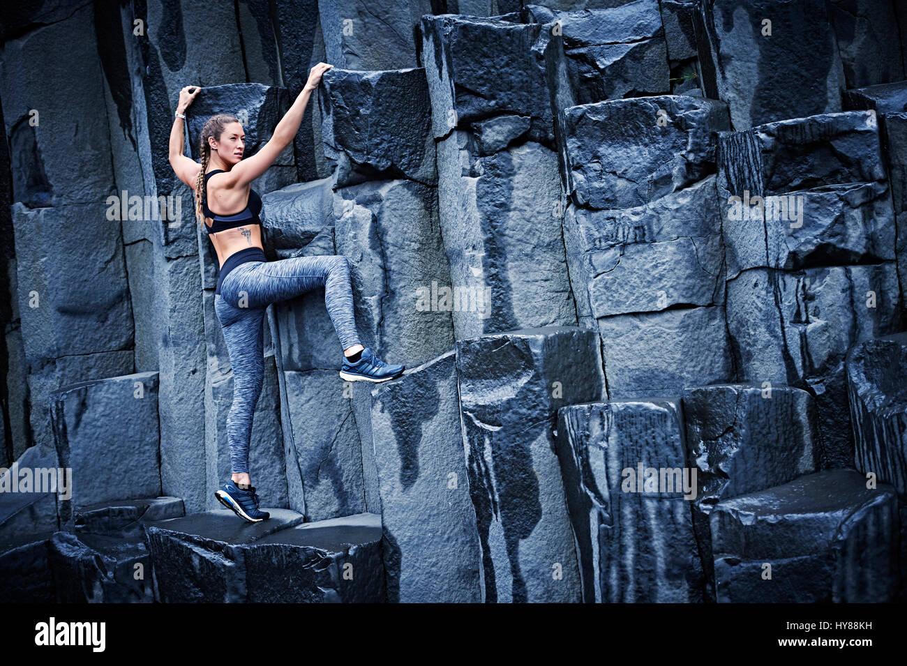 Felice fiducioso giovani donne di arrampicata su roccia di basalto nel sud dell'Islanda Immagini Stock