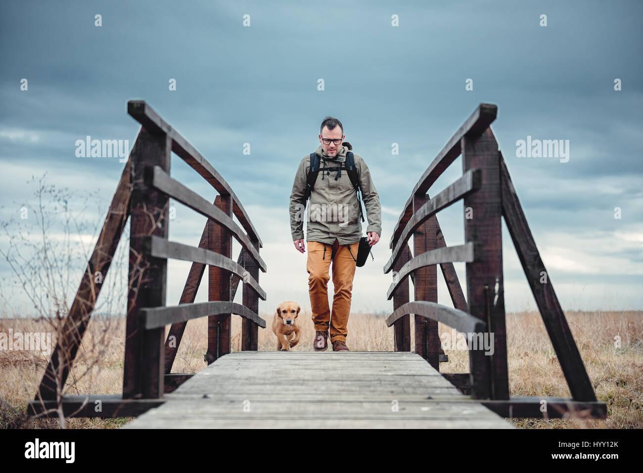 Escursionista e cane attraversando il ponte in legno sul giorno nuvoloso Immagini Stock