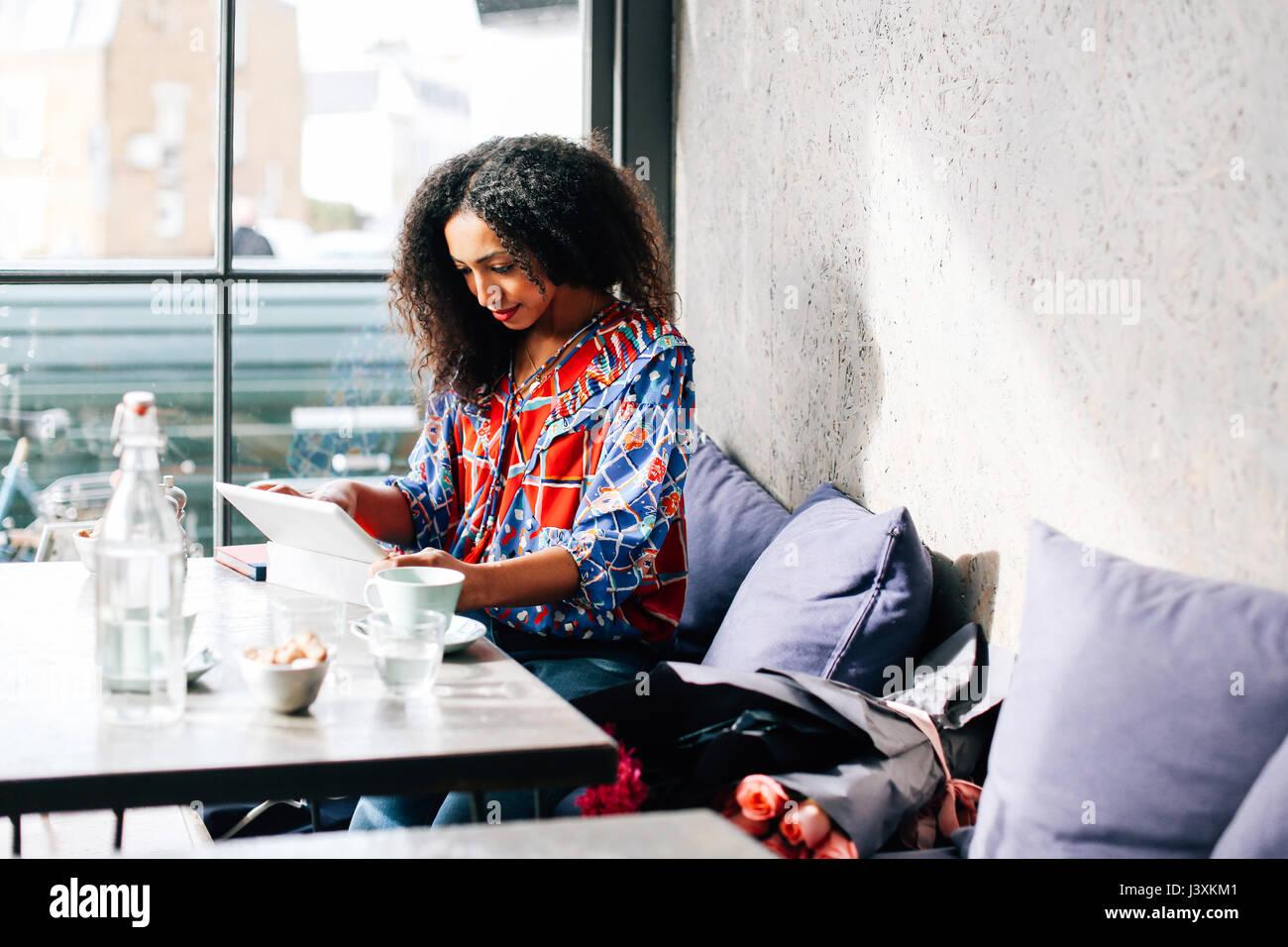 Metà donna adulta con tavoletta digitale in cafe Immagini Stock