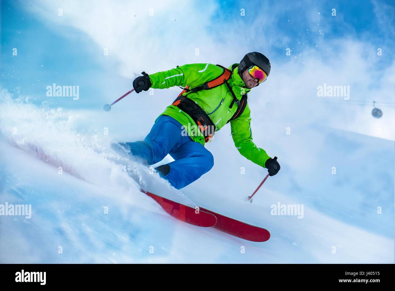 Sorprendente colpo di un colorato vestito con rifiniture a sciare sulla neve onda. Immagini Stock
