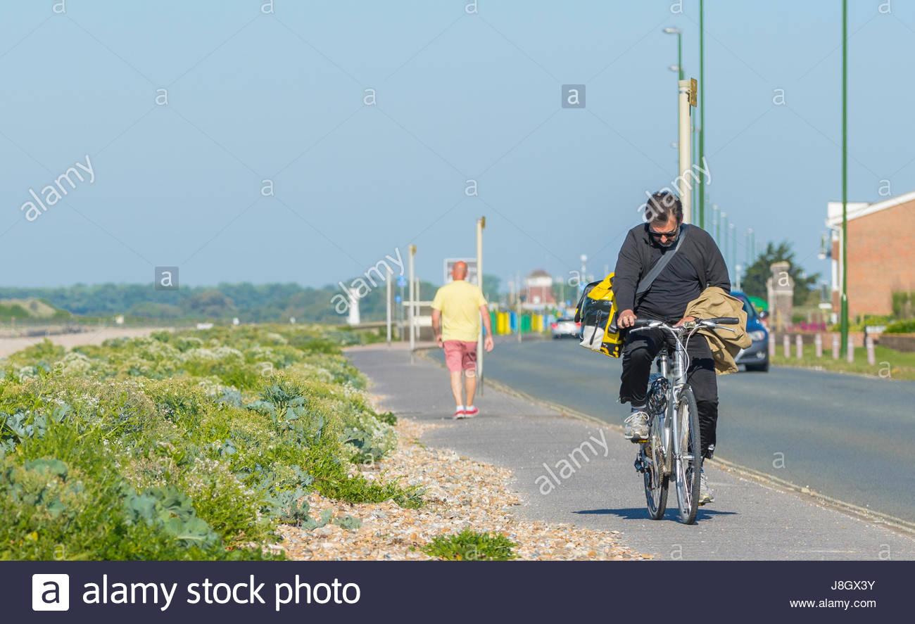 Uomo in bicicletta sul marciapiede mentre guardando un telefono. Immagini Stock